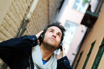 Close-up of man listening to music with hands on headphones