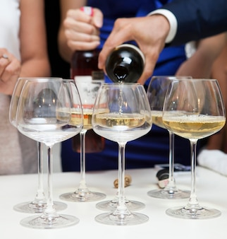 Close-up of man pouring white wine