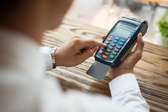Close-up of man using payment terminal in shop