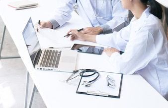 Close up of patient and doctor taking notes or Professional medical doctor in white uniform gown coat interview