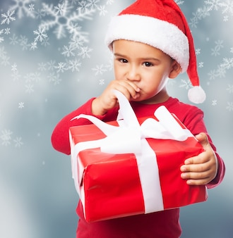 Close-up of pensive little boy with a present