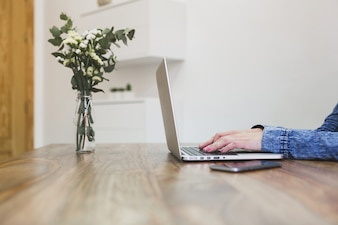 Close-up of person using her laptop on a wooden table