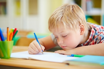 Close-up of primary student learning to write