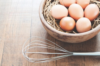 Close-up of raw chicken eggs in wooden bowl on wood background with kitchen utensil