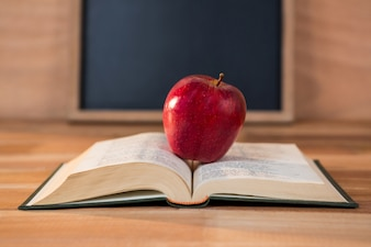 Close up of red apple with open book