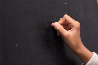 黒板に右手の書き込みのクローズアップ