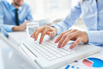 Close-up of secretary typing on laptop