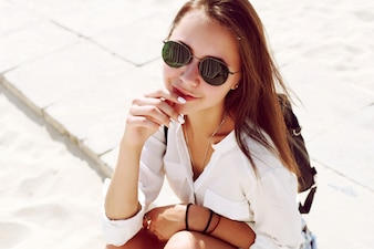 Close-up of sensual woman with sunglasses sitting on the beach
