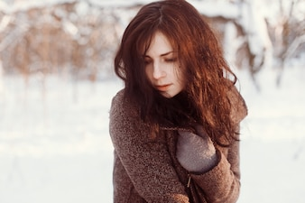 Close-up of shy woman posing in the snow