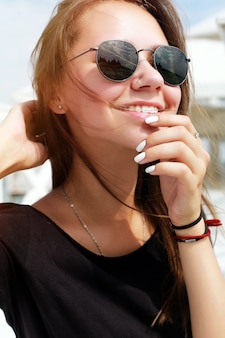 Close-up of smiling woman with sunglasses and touching her chin