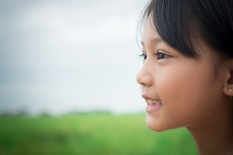 Close up of sweet little girl outdoors with smiling in the summe