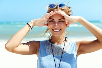 Close-up of tanned woman laughing on the beach