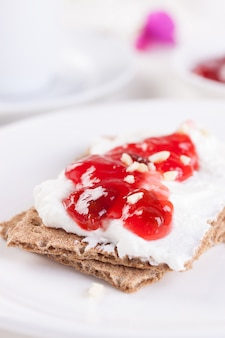 Close-up of tasty strawberry jam with crispy toasts