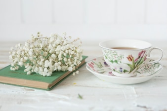 Close-up of tea cup, flowers and book