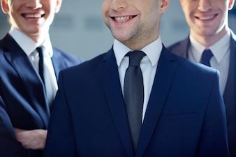 Close-up of three smiling executives