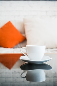 Close-up of white cup with sofa background