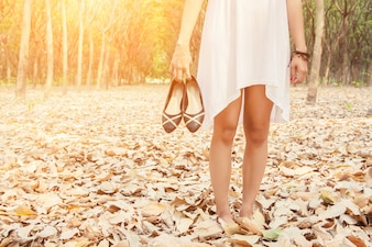 Close-up of woman carrying her shoes in hand