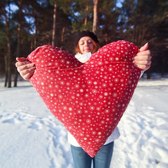 Close-up of woman holding a heart-shaped cushion