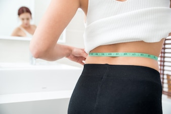 Close-up of woman measuring waist in bathroom