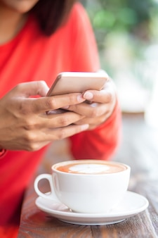 Close-up of woman texting sms in coffee shop