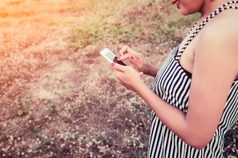 Close-up of woman using her phone in the field