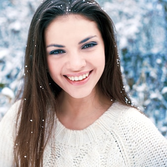 Close-up of woman with a big smile and snowflakes on the head