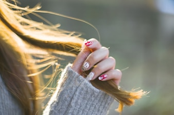Close-up of woman with painted nails touching her hair