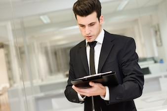Close-up of young businessman reading a document