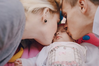 Close-up of young parents kissing their daughter