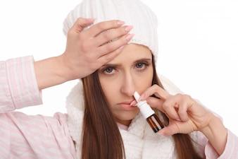 鼻スプレーを保持している若い女性のクローズアップ