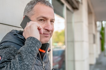 Close up portrait of happy mature guy talking on cell phone and smiling