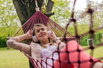 Close up portrait of woman lying down on hammock listening to music with cell phone. Cheerful girl enjoy in red hammock outdoor. woman relaxing outside listening to music with earphones