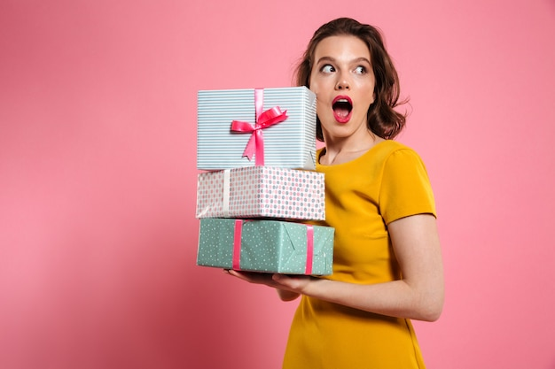 Close-up portrait of shocked pretty girl with bright makeup holding heap of presents, looking aside