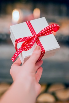 Close up shot of female hands holding a small gift wrapped with red ribbon. Small gift in the hands of a woman indoor. Female Holding Rustic Decorated Gift with Red  Ribbon