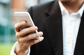 Close-up smart Business man wearing modern black suit and white shirt and texting on mobile smart phone