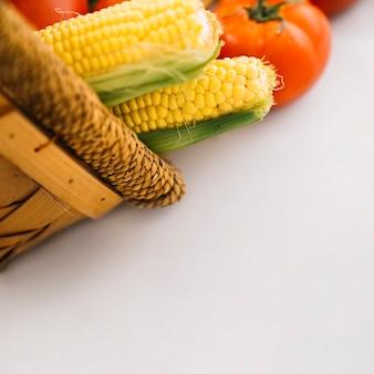 Крупный план кукурузы и помидоров в корзине