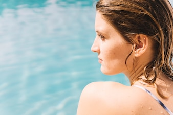 Close up view of woman sitting by the pool