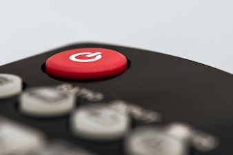 Closeup image of a red power button on a remote control for a TV or another entertainment device.
