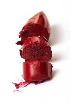 Closeup of broken beautiful classic red lipstick. Fashion.