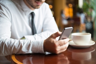 Closeup of Business Leader With Smartphone in Cafe