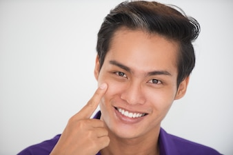Closeup of Smiling Asian Man Touching Cheek