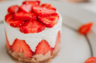 Closeup of strawberry cake with fresh strawberry on wooden background. Homemade strawberry cake. Cheesecake with Strawberry