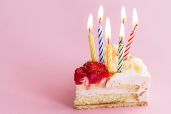 Closeup of tasty beautiful appetizing elegant piece of birthday cake with many candles. Birthday Holiday Concept.