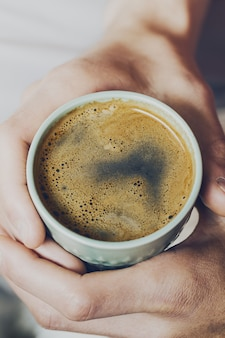 Closeup of tasty coffee espresso with tasty yellow foam in green ceramic cup. Male hands holding warm hot drink. Toning.