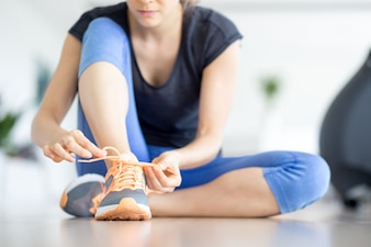 Closeup of Woman Tying Shoelace on Gym Floor