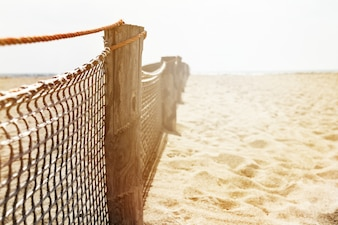 Closeup of Wooden Old Fence on Beach. Day Light. Sunny Light. Horizontal. Copy Space.