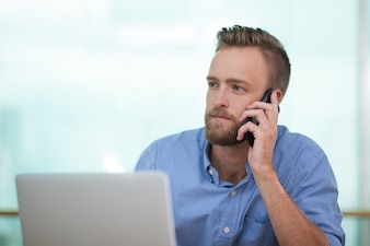 Closeup of Young Man Calling on Phone with Laptop