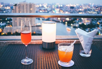 Cocktail glasses with candle light in rooftop bar against city view
