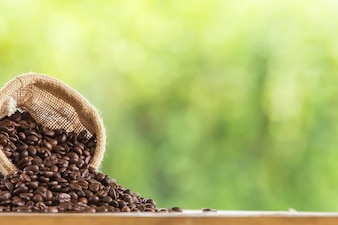 木製の卓上に灰色の背景をぼかして茶色のコーヒー豆