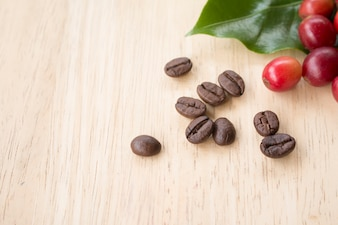 Coffee berry and coffee beans on wooden panel